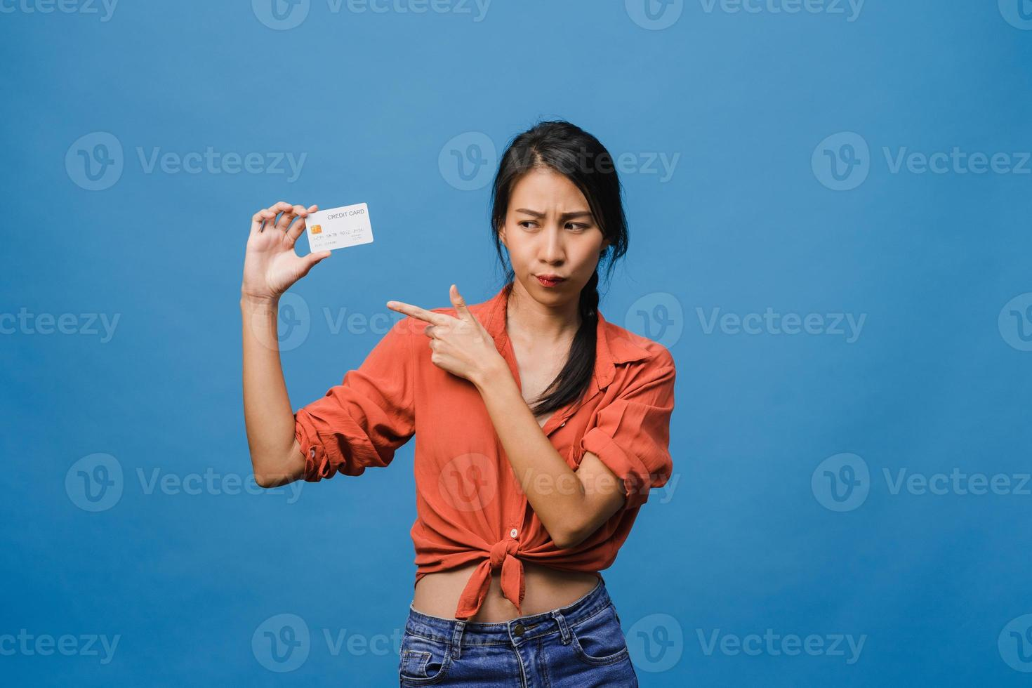 la giovane donna asiatica mostra la carta di credito con l'espressione positiva, sorride ampiamente, vestita con abiti casual sentendo felicità e stando isolata su sfondo blu. concetto di espressione facciale. foto