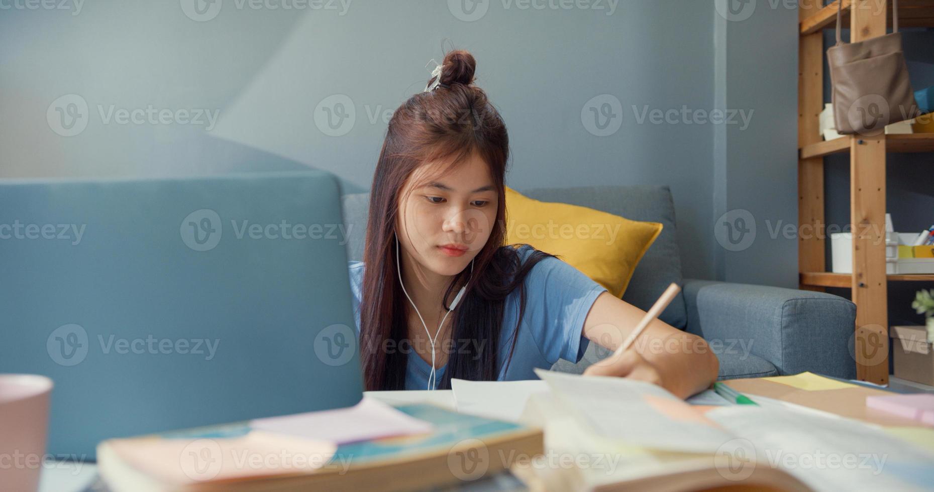 giovane ragazza asiatica adolescente con cuffie per abbigliamento casual usa il computer portatile impara a scrivere online il quaderno delle lezioni nel soggiorno di casa. isolare l'istruzione online e-learning concetto di pandemia di coronavirus. foto