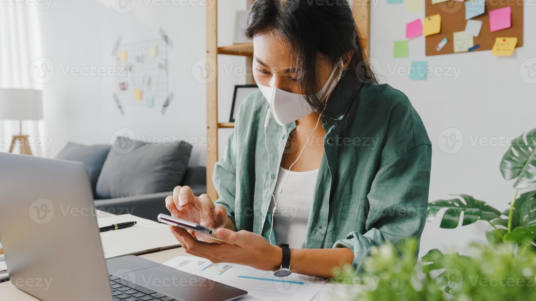 le donne freelance asiatiche indossano la maschera facciale utilizzando lo smartphone che acquista online tramite il sito Web mentre sono sedute alla scrivania in soggiorno. lavoro da casa, lavoro a distanza, distanziamento sociale, quarantena per coronavirus. foto