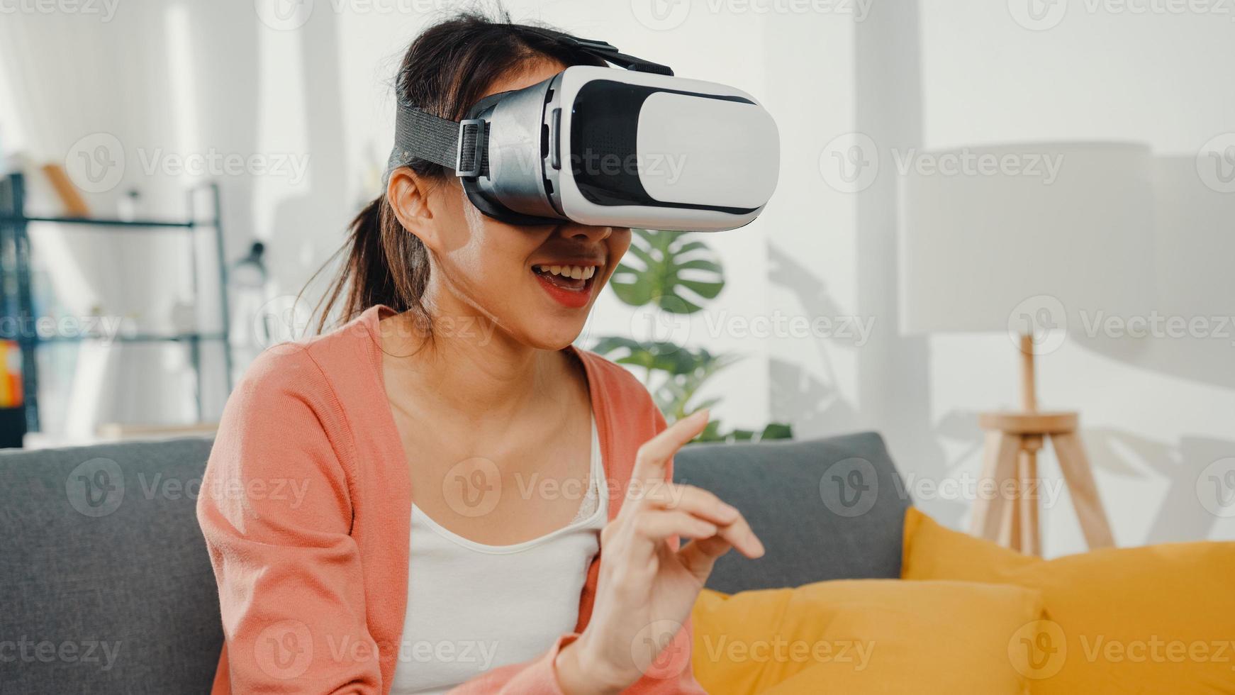 signora asiatica che indossa gli occhiali auricolare della mano gesticolante della realtà virtuale seduta sul divano nel soggiorno di casa. resta a casa quarantena covid, re-immaginando la realtà, tecnologia vr del concetto futuro. foto