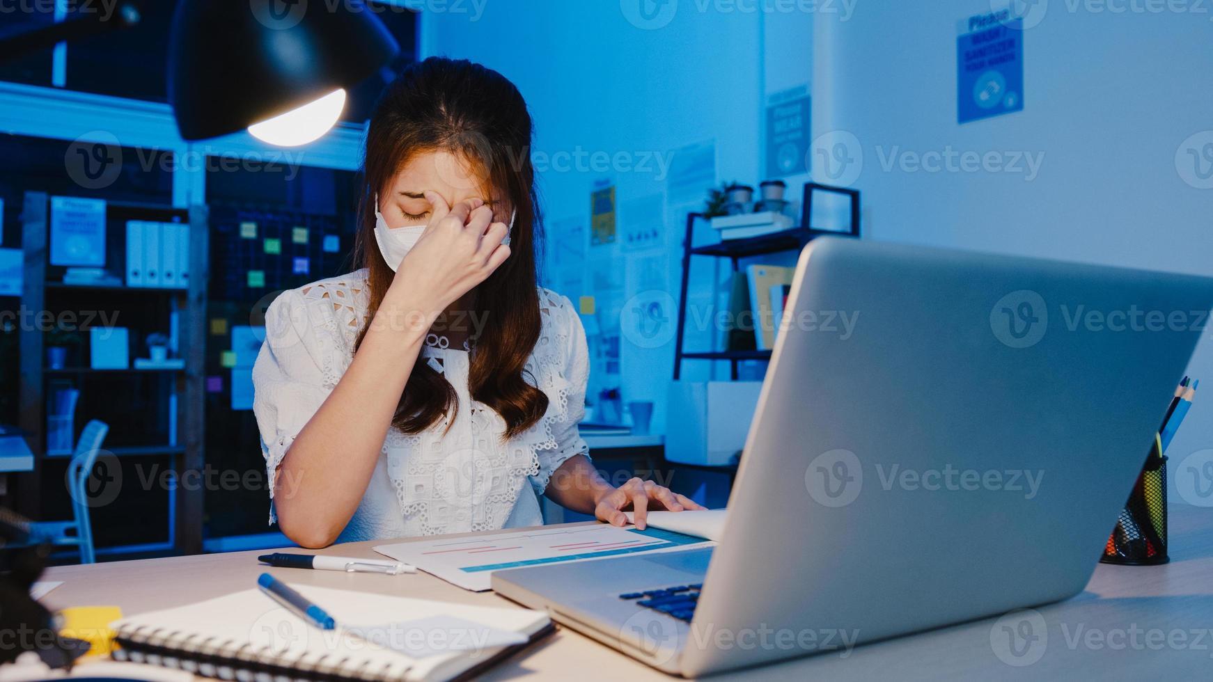 le donne asiatiche freelance indossano la maschera facciale usando il duro lavoro del laptop nel nuovo normale ufficio a casa. lavoro da sovraccarico domestico di notte, autoisolamento, distanza sociale, quarantena per la prevenzione del virus corona. foto
