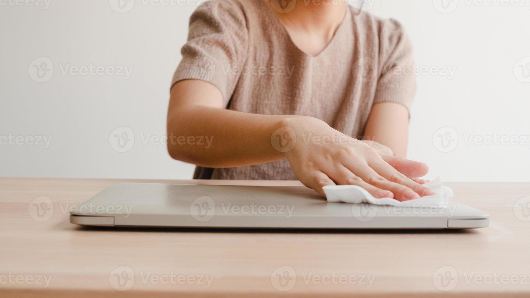 donna asiatica che usa spray alcolico su un laptop pulito in tessuto prima dell'apertura per proteggere il coronavirus. computer pulito femminile per l'igiene quando il distanziamento sociale resta a casa e il tempo di autoquarantena. foto