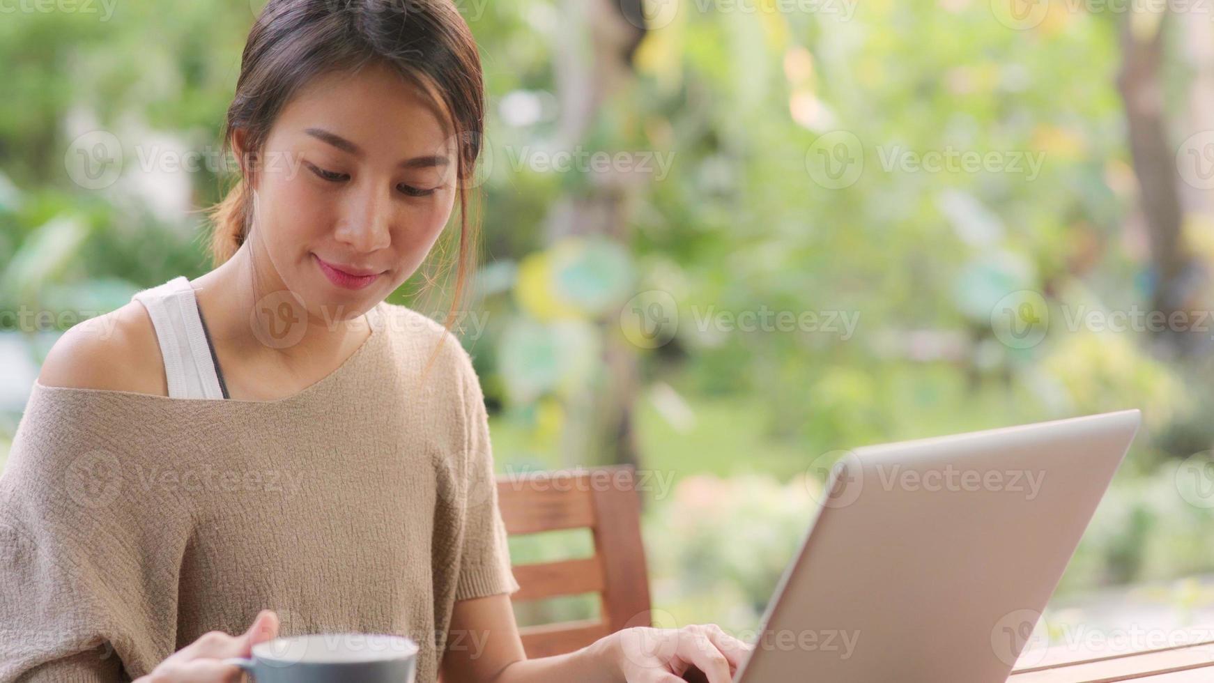 donna asiatica freelance che lavora a casa, donna d'affari che lavora al computer portatile e beve caffè seduta sul tavolo in giardino al mattino. donne di stile di vita che lavorano a casa concetto. foto