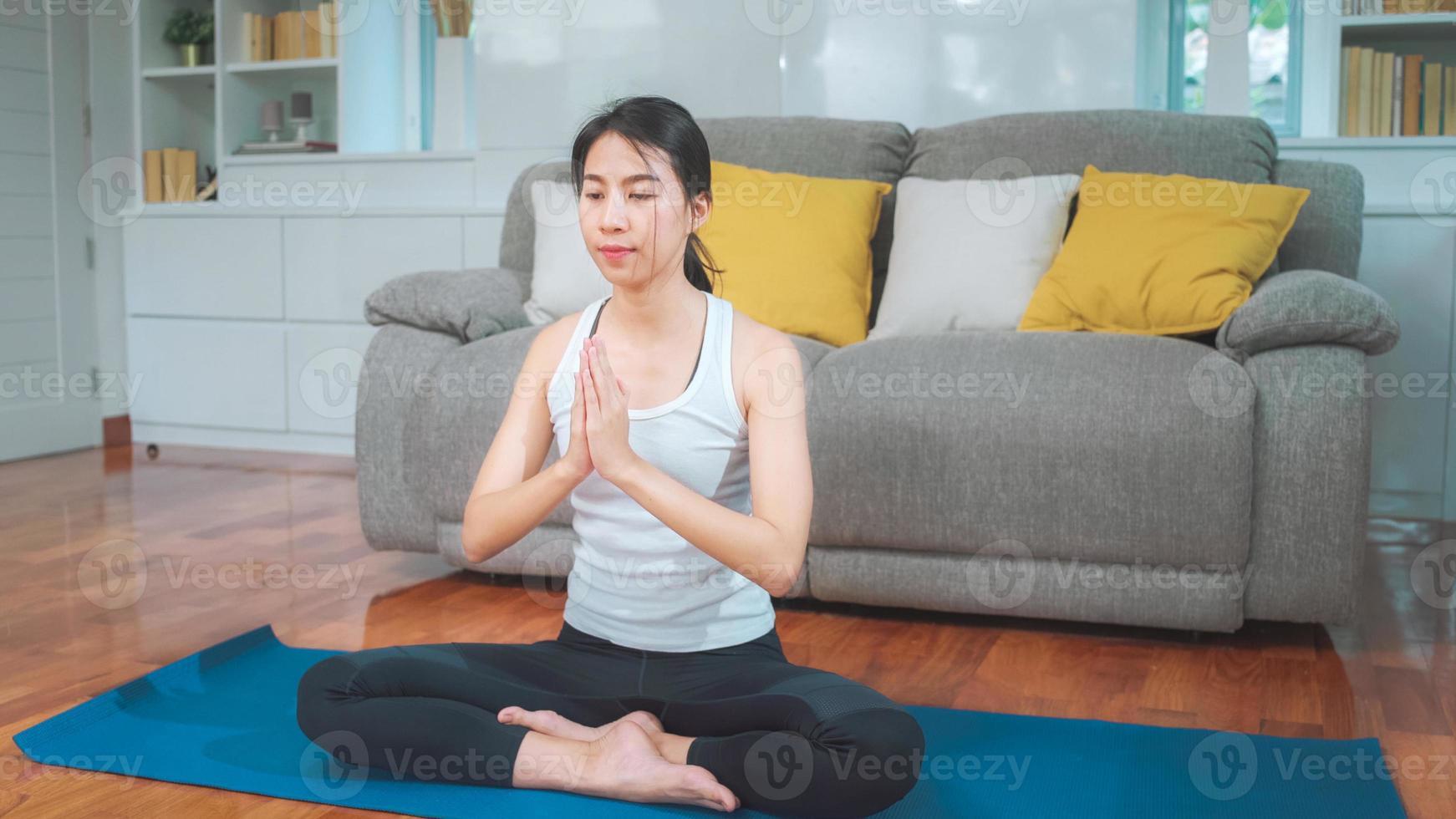 giovane donna asiatica che pratica yoga nel soggiorno. bella femmina attraente che risolve per sano a casa. concetto di esercizio della donna di stile di vita. foto