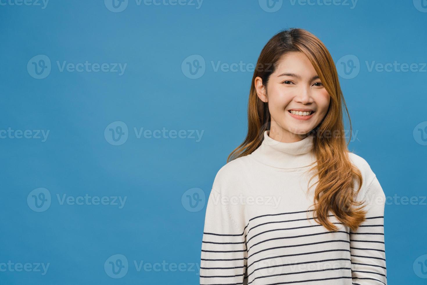 giovane donna asiatica con espressione positiva, sorriso ampiamente, vestita con abiti casual e guardando la telecamera su sfondo blu. felice adorabile donna felice esulta successo. concetto di espressione facciale. foto
