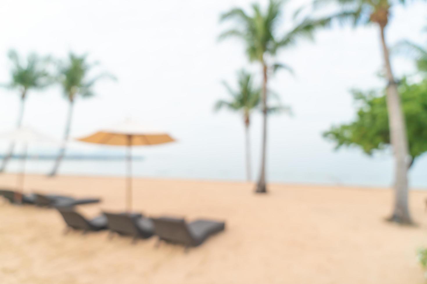 Sfocatura astratta sedia da spiaggia sulla spiaggia con mare oceano per lo sfondo - concetto di viaggio e vacanza foto