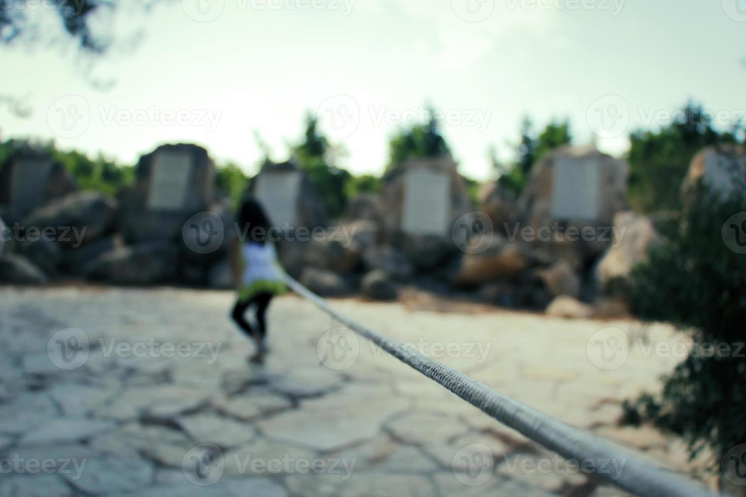 giovane ragazza che cerca di andare in lontananza mentre è legata da una corda foto