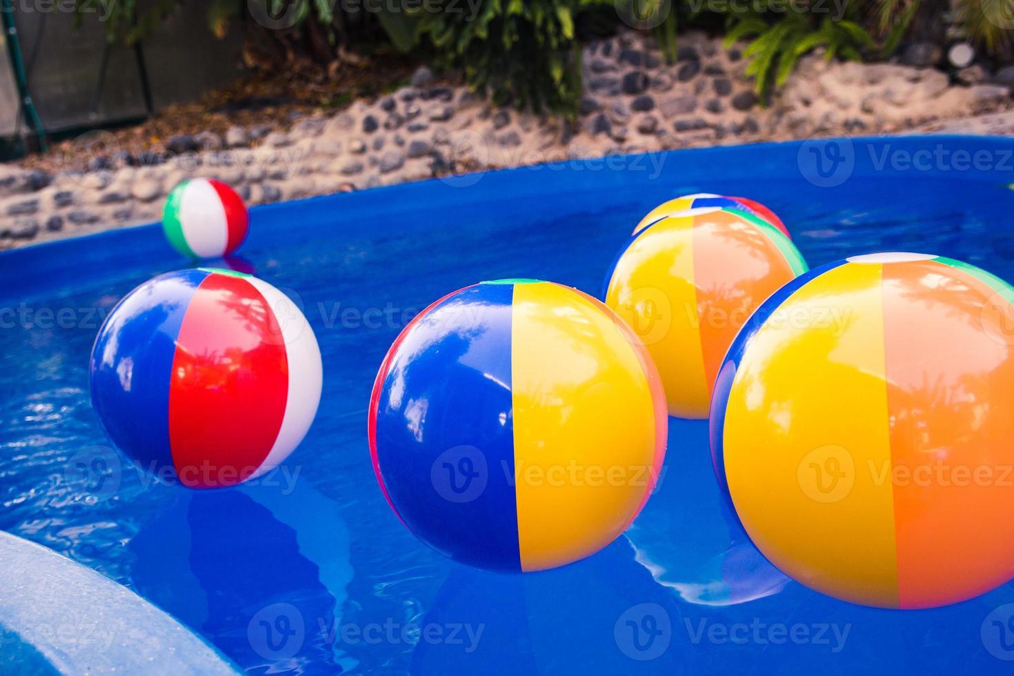 palloni da spiaggia colorati che galleggiano in piscina foto