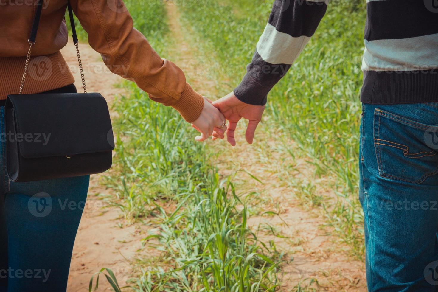 giovane coppia che si tiene per mano sullo sfondo dell'erba verde foto