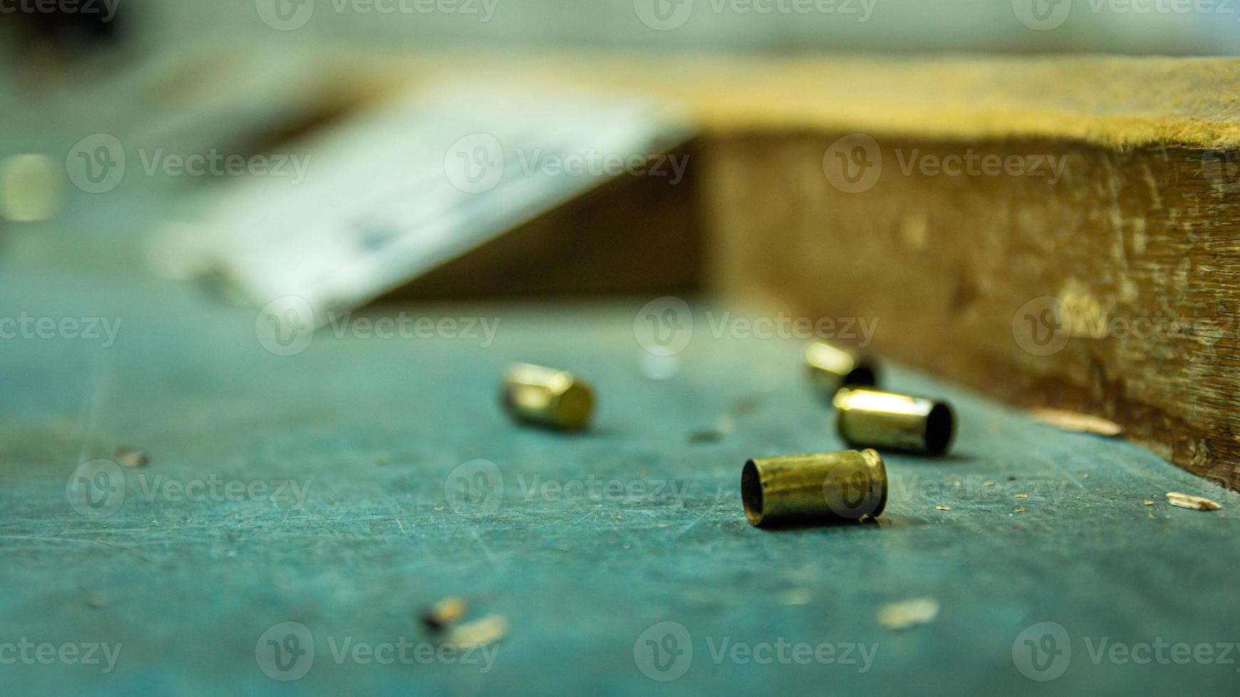 proiettili di pistola vuoti sul tavolo di legno in un poligono di tiro foto