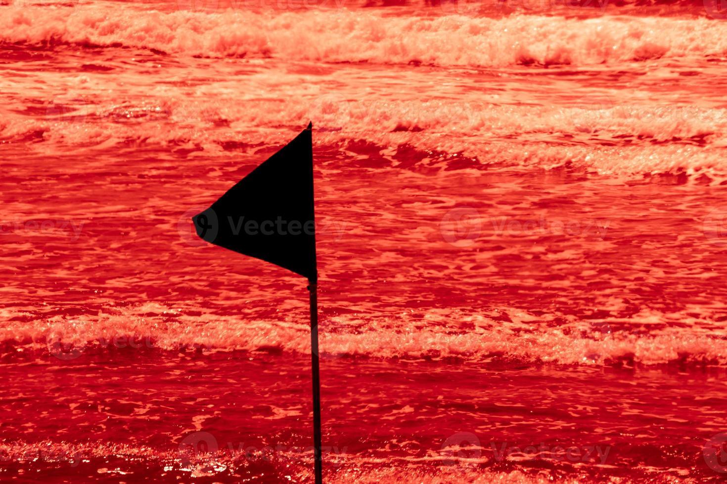 bandiera nera di avvertimento che segna il limite dell'area di nuoto sicura in una bellissima spiaggia con cielo blu e mare turchese in israele foto