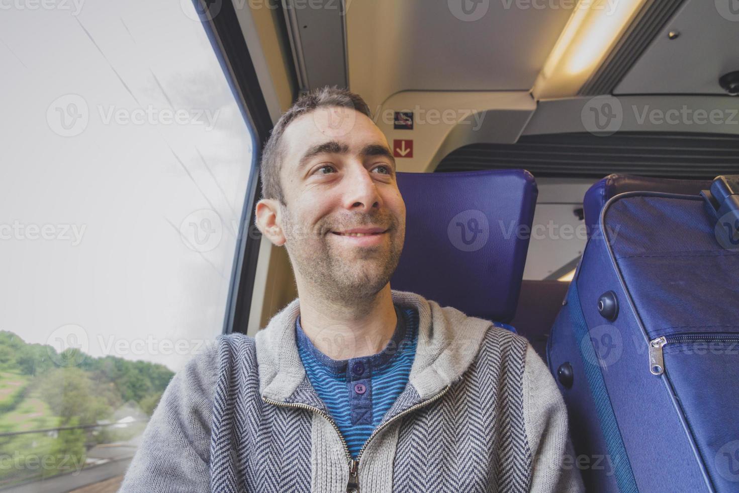 giovane che viaggia su un treno e sorride a qualcuno foto