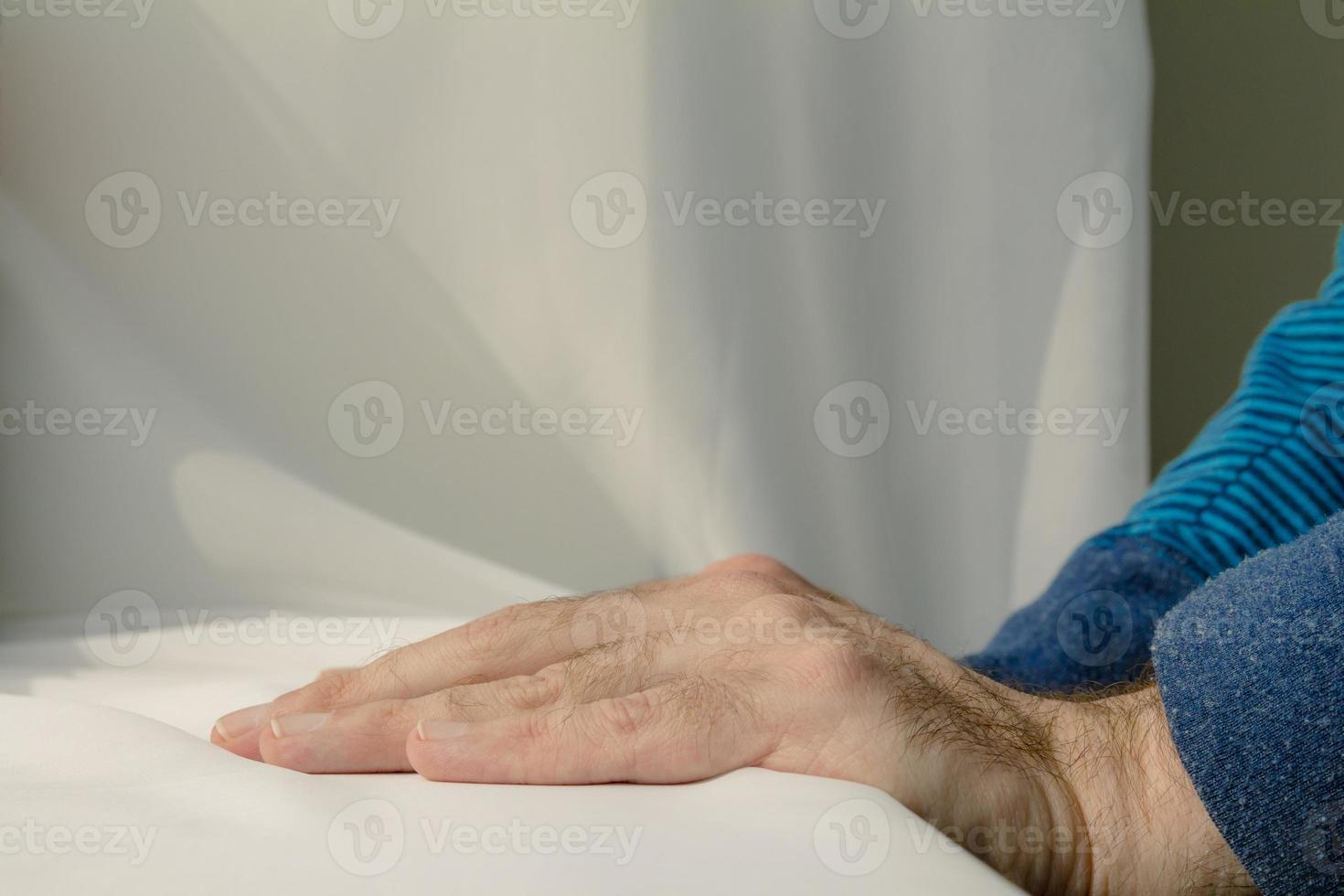 uomo che si appoggia e mette le mani in basso su uno sfondo di stoffa bianca foto