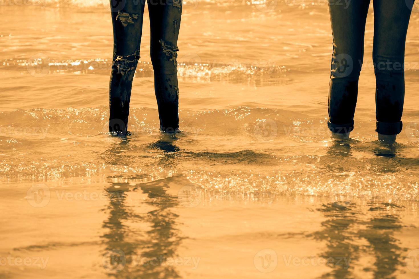 gambe di donne in blue jeans in piedi nell'acqua di mare sulla costa - tono dorato foto