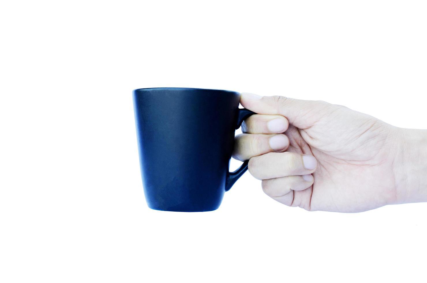 mano che tiene tazze blu isolate su sfondi bianchi foto