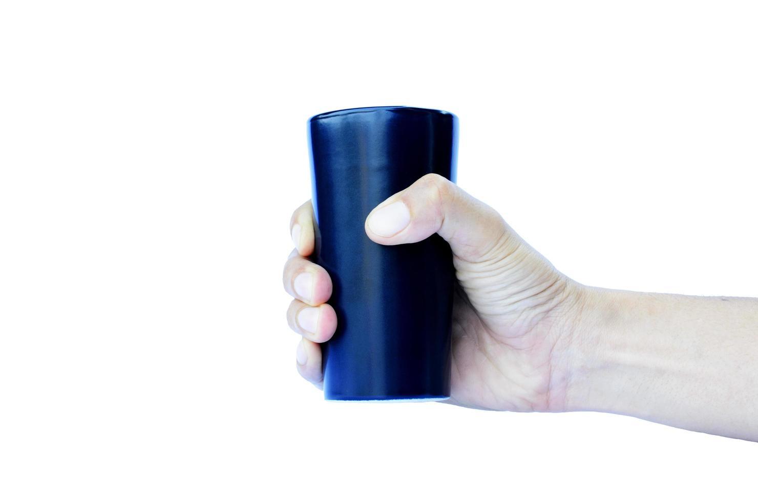 mano destra che tiene tazza blu in ceramica isolata su sfondi bianchi foto