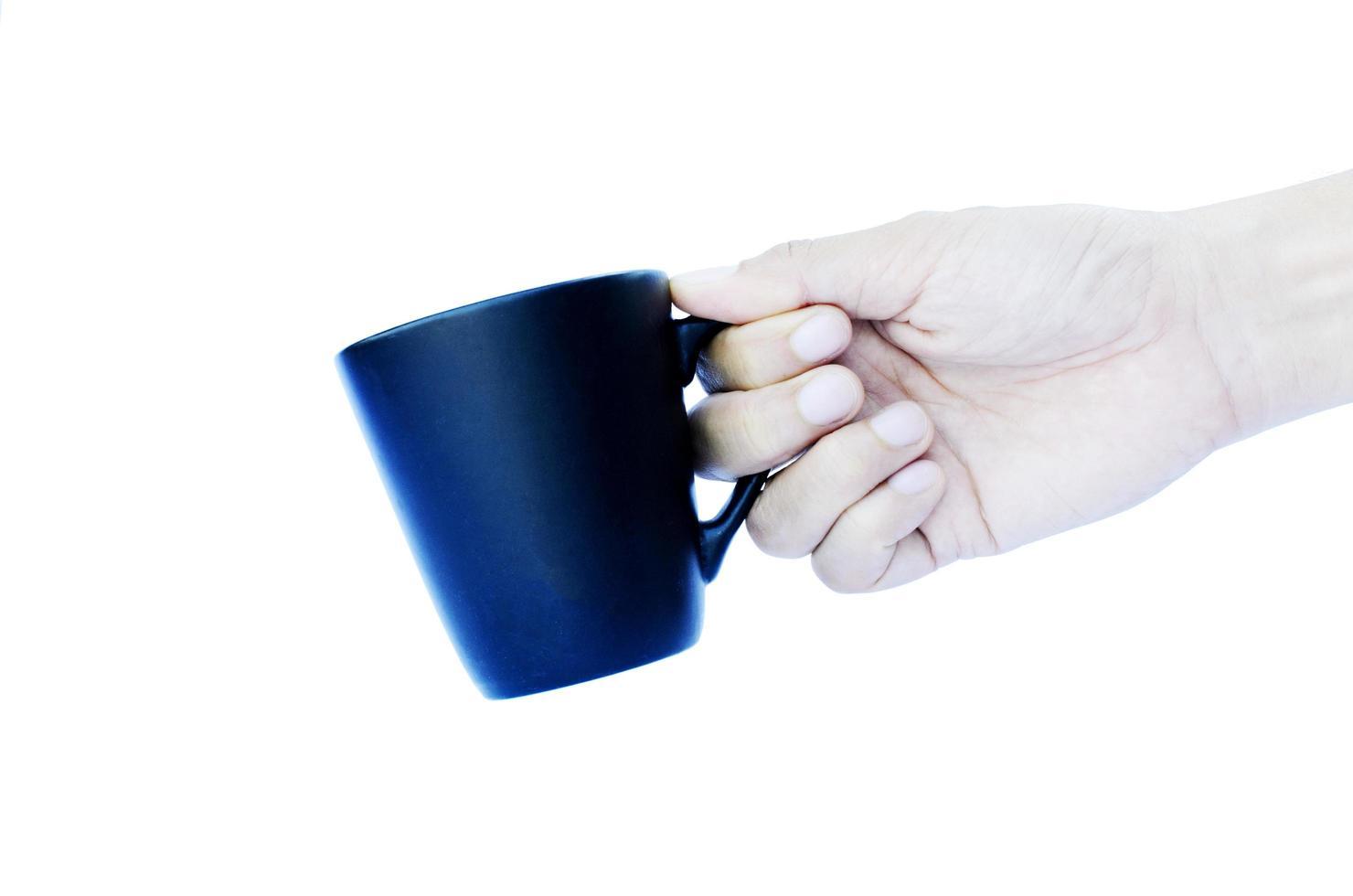 mano destra che tiene tazze blu isolate su sfondi bianchi foto