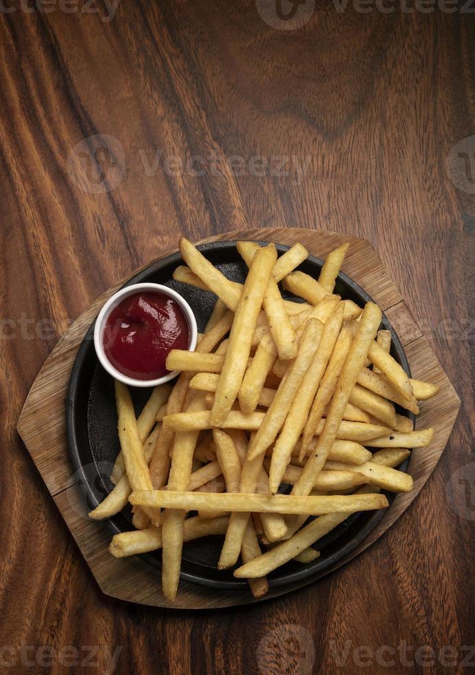 porzione di patatine fritte snack su tavola di legno sfondo foto