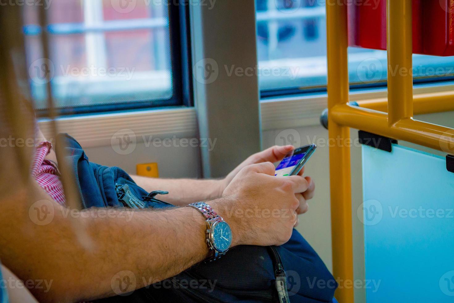 primo piano su un uomo che utilizza uno smartphone mentre viaggia in autobus a Varsavia, Polonia foto