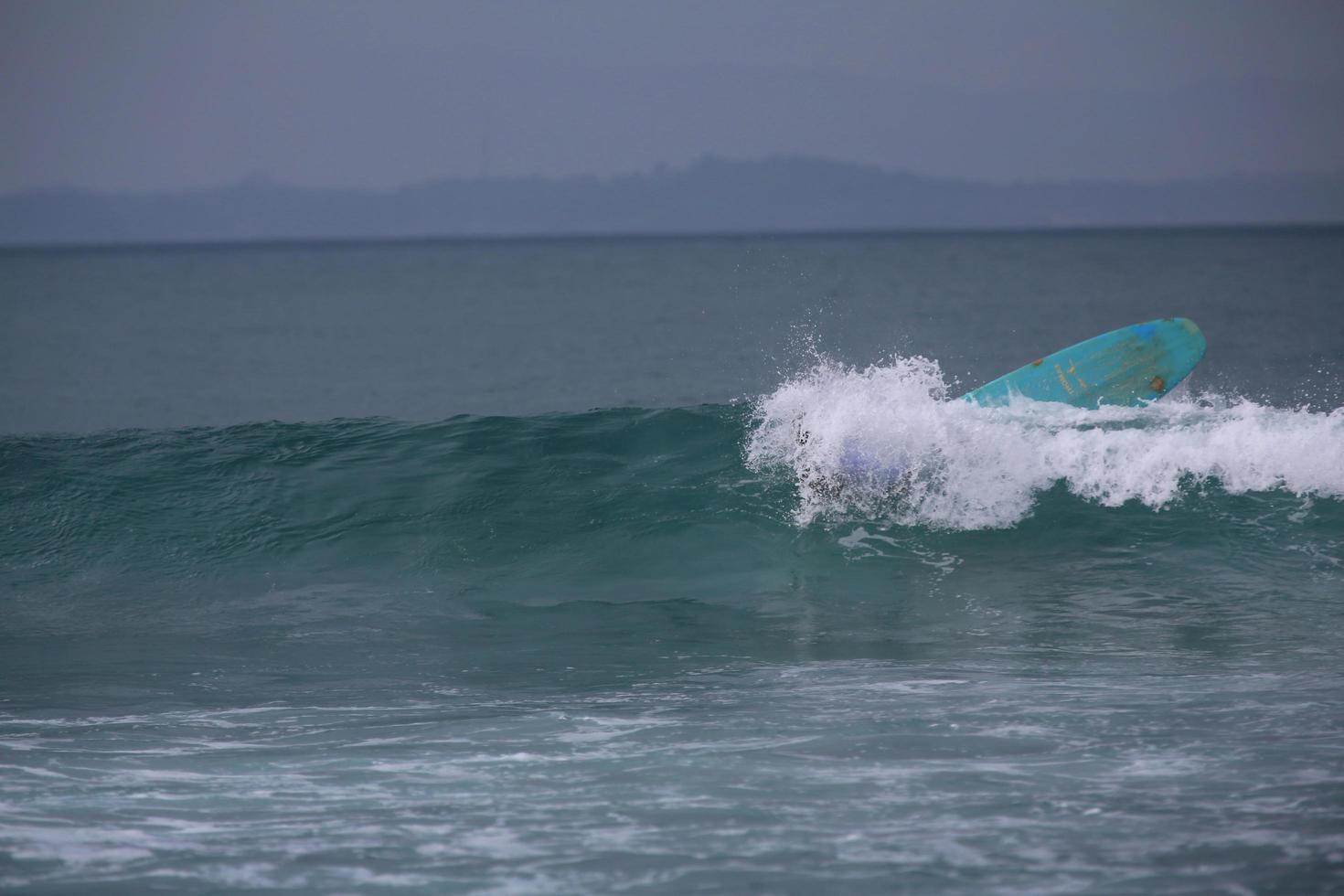 tavola da surf inversa nell'oceano foto