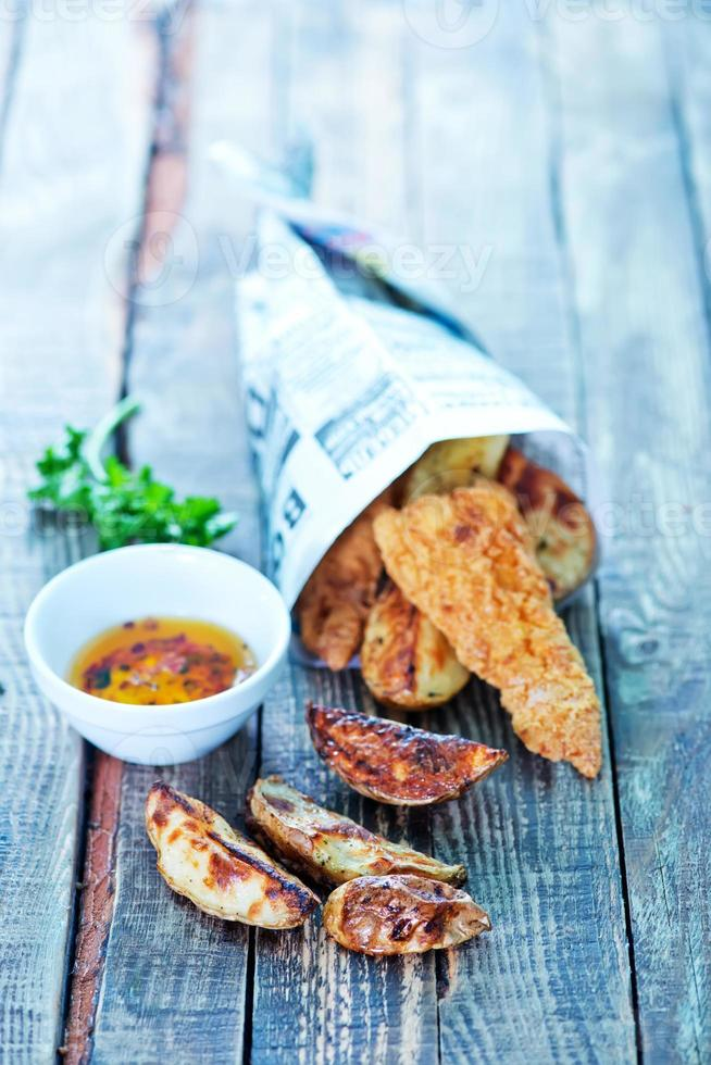 primo piano di pesce appena fatto e patatine fritte con tuffo e contorno foto