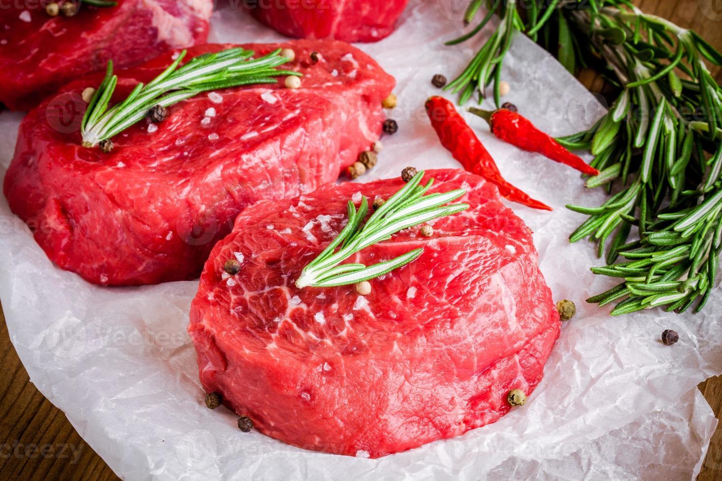 due bistecche crude con rosmarino, aglio, sale e pepe foto