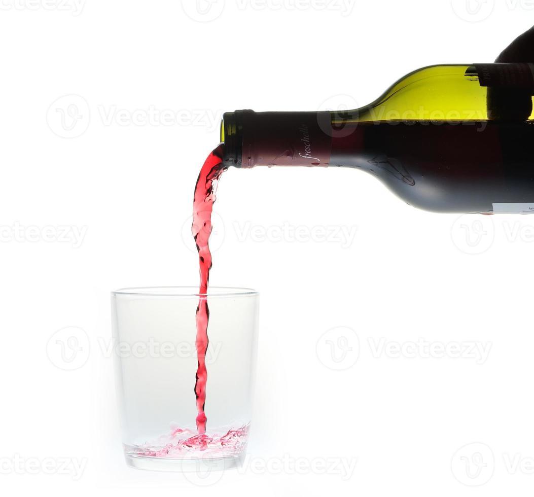 bottiglia di vino versando liquido in un bicchiere di vetro foto
