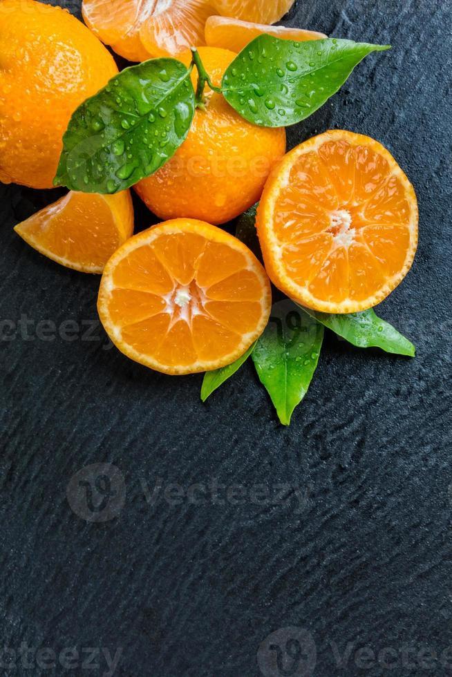 mandarino fresco su pietra nera foto