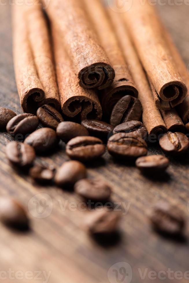 bastoncini di caffè e cannella su sfondo di legno vicino vertica foto