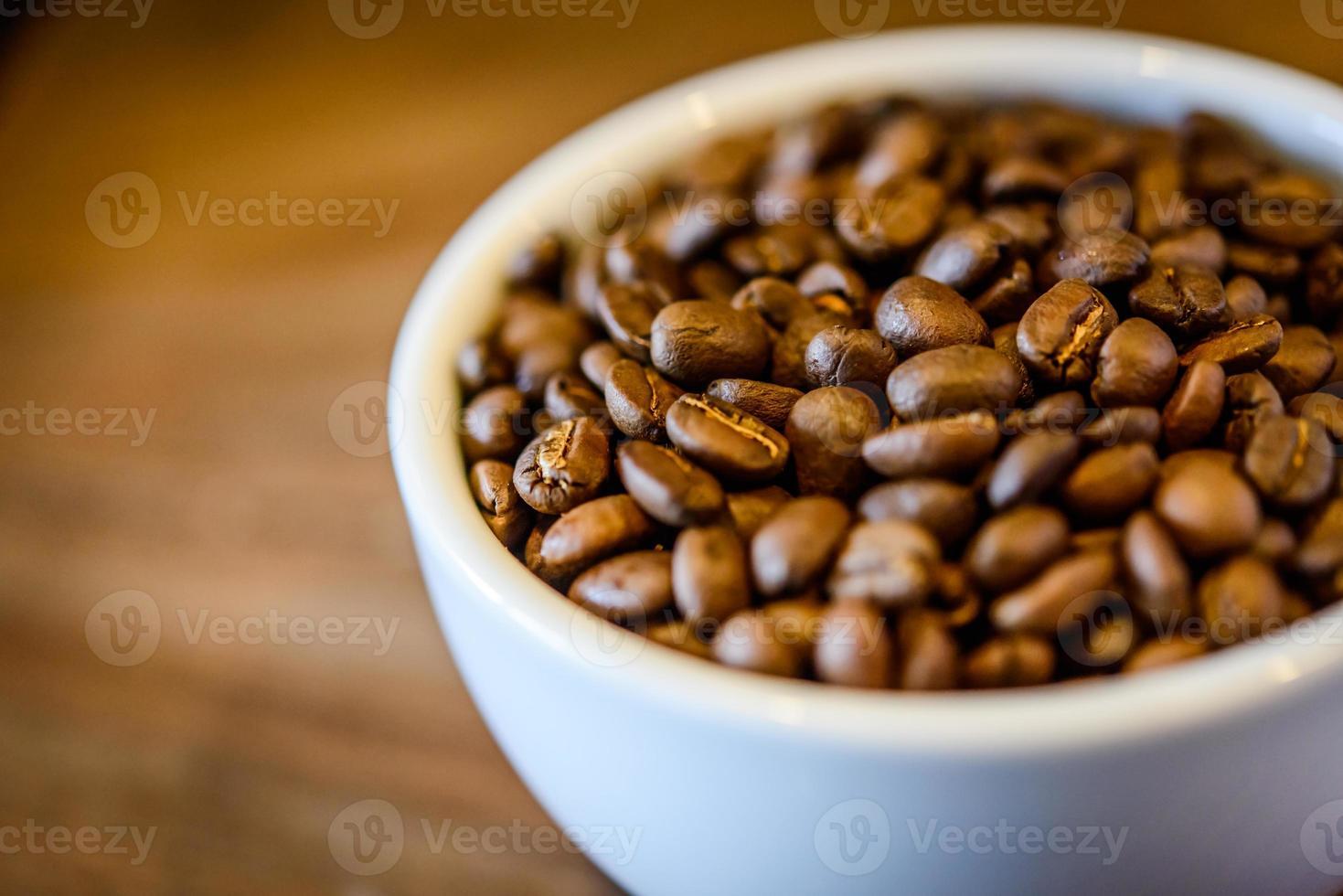 chicchi di caffè in tazza su sfondo di legno grunge foto