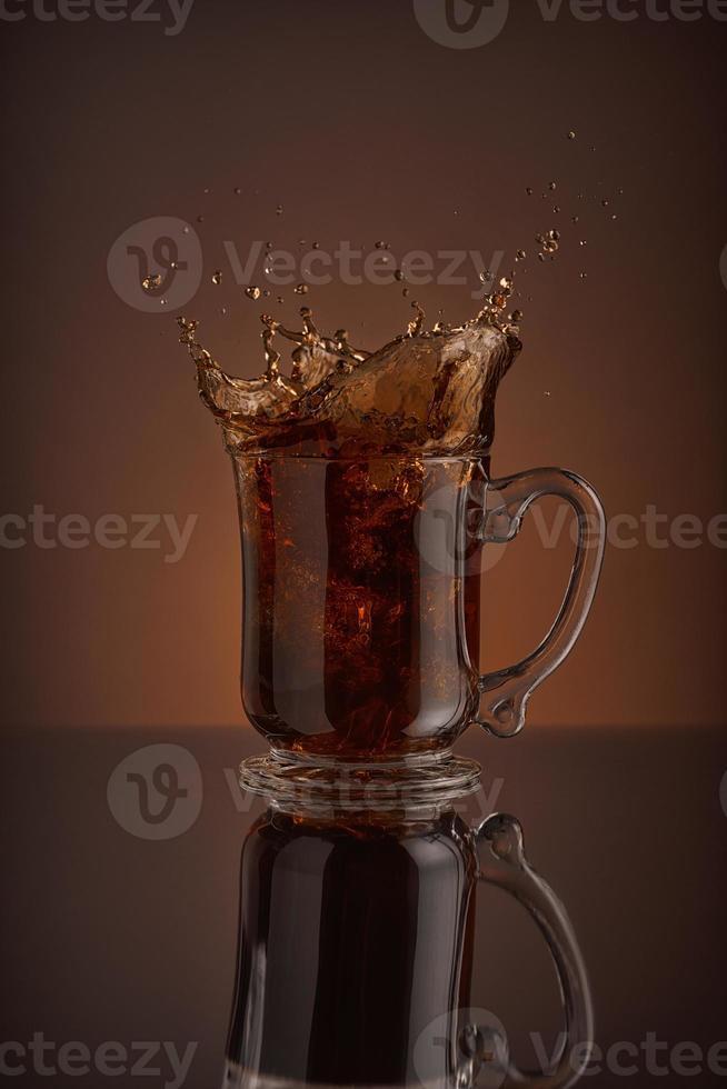 spruzzata di bevanda di caffè di ghiaccio su uno sfondo marrone. foto