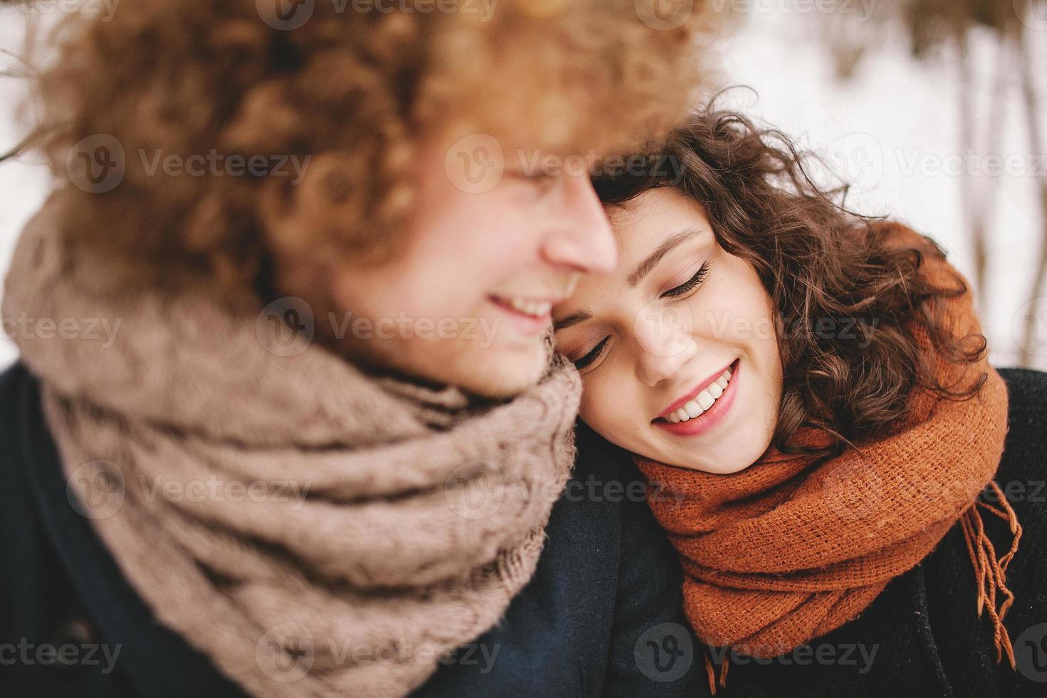giovane coppia seduta insieme nella foresta invernale foto