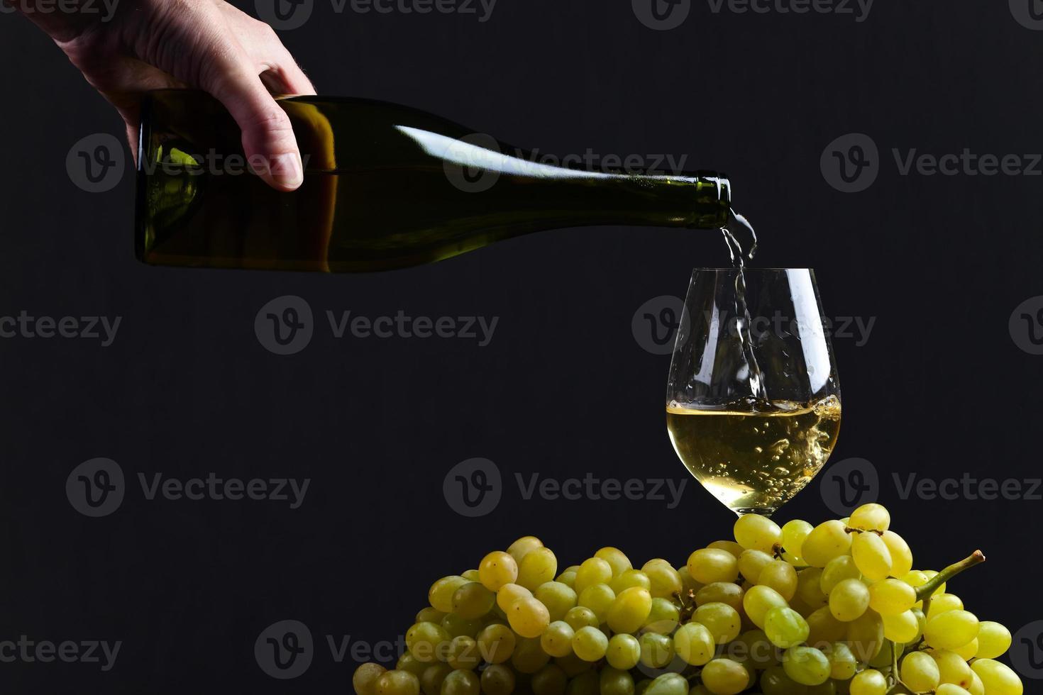 il vino viene versato in un bicchiere da vino foto