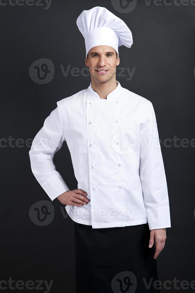 cuoco cuoco su sfondo scuro, sorridente con cappello foto