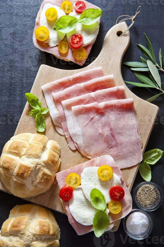 panino con prosciutto, pomodorini, olive verdi e nere, basi foto