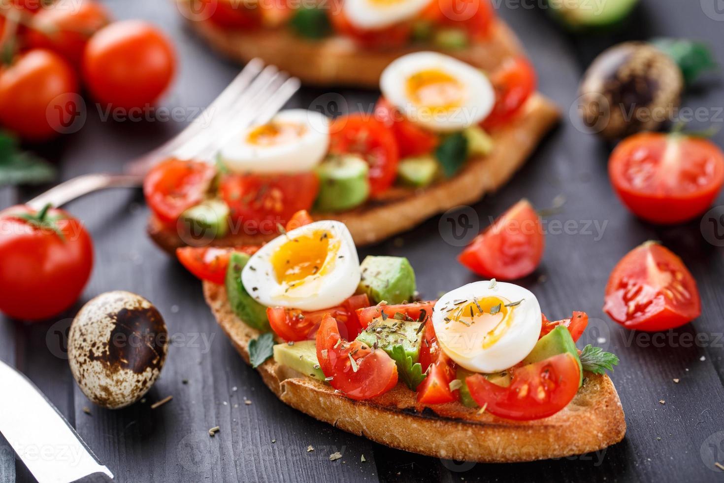 bruschetta con pomodoro, avocado e uovo di quaglia foto