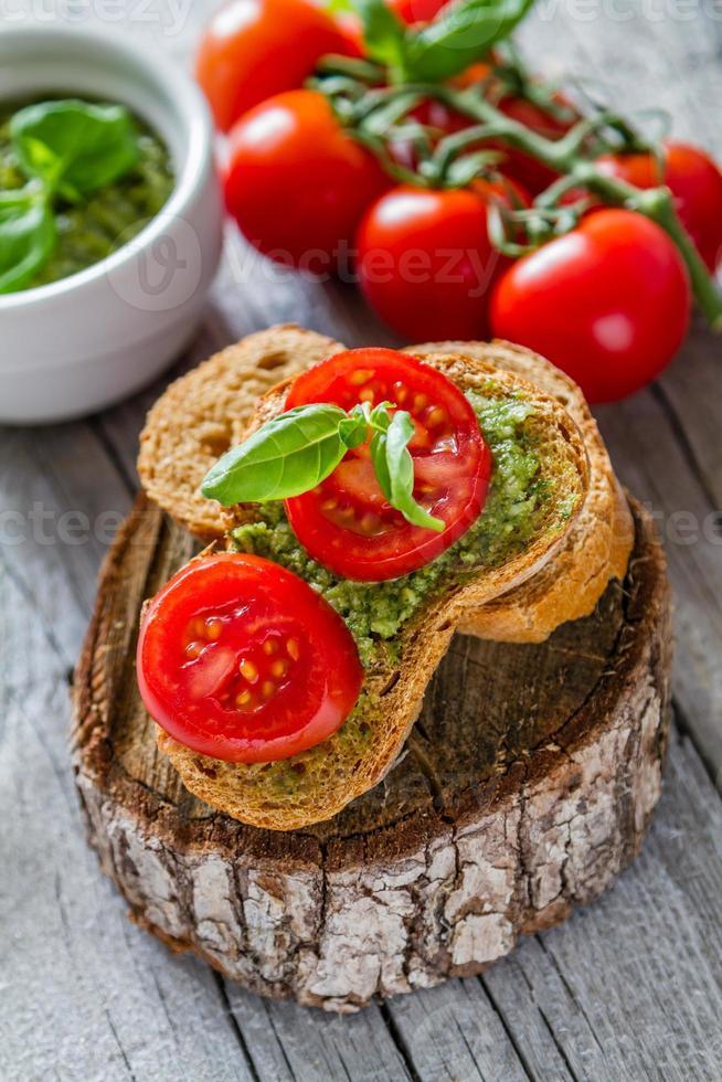 pesto in una ciotola bianca, toast, pomodori, aglio, formaggio foto