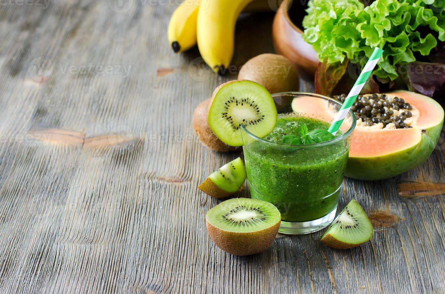 frullato verde con kiwi, papaia e foglie di insalata copia spazio foto