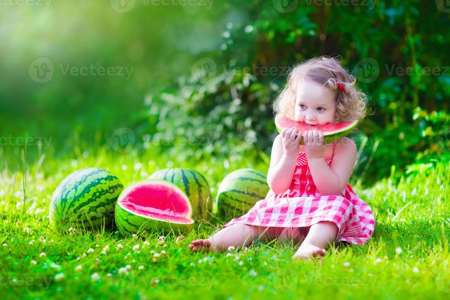 bambina adorabile che mangia anguria foto