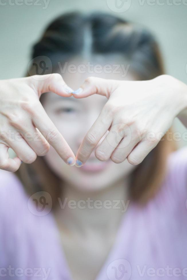 giovane donna felice dell'Asia che fa il segno del cuore con le mani foto