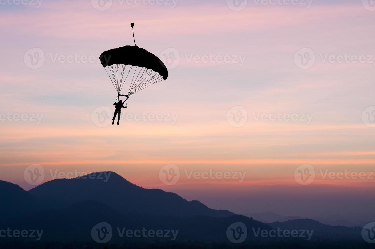 paracadute al tramonto che si staglia foto