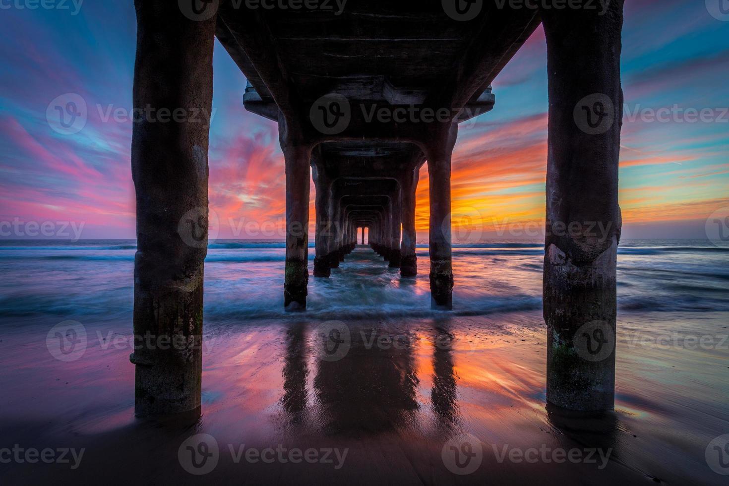 sotto un molo sull'oceano al tramonto foto