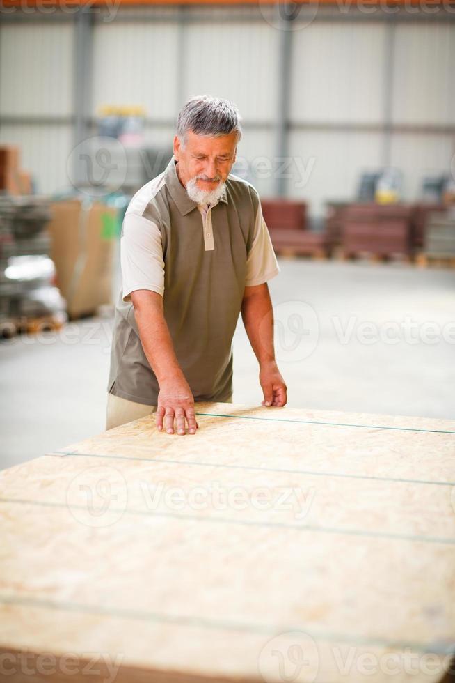 uomo anziano acquisto legname da costruzione in un negozio fai da te foto