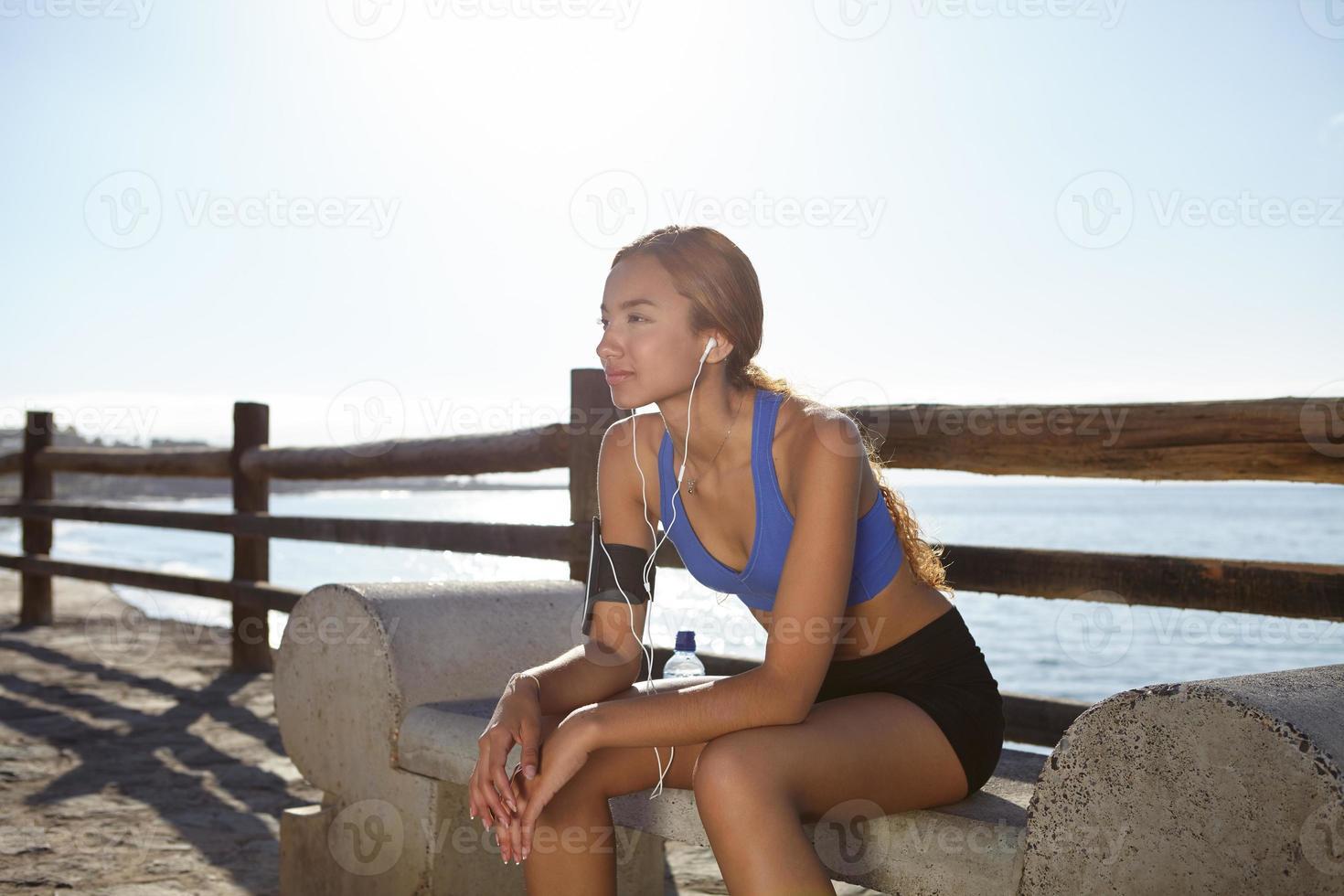 giovane atleta seduto fuori in estate foto