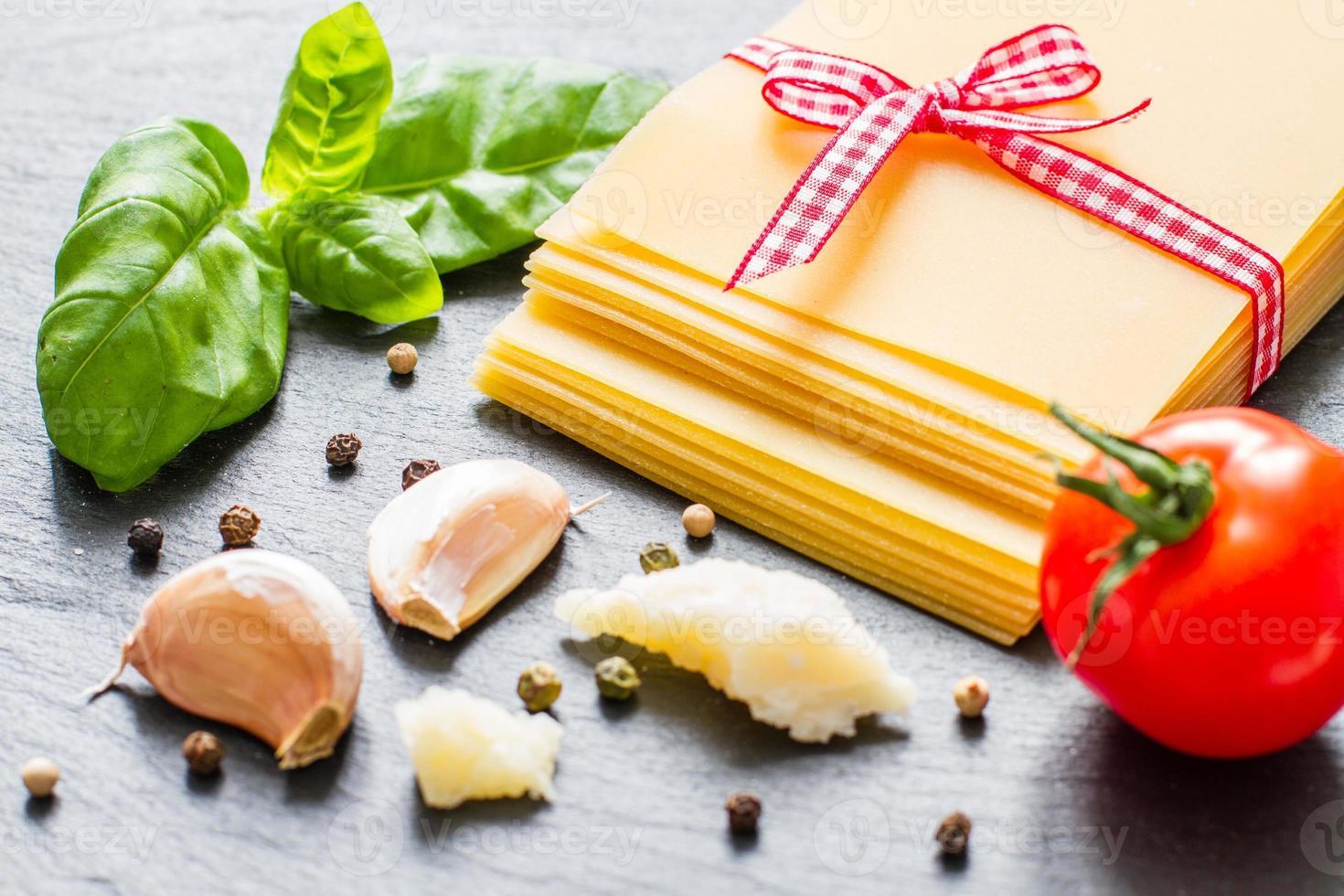 ingredienti lasagne - fogli asciutti, pomodorini, basilico, aglio, formaggio foto
