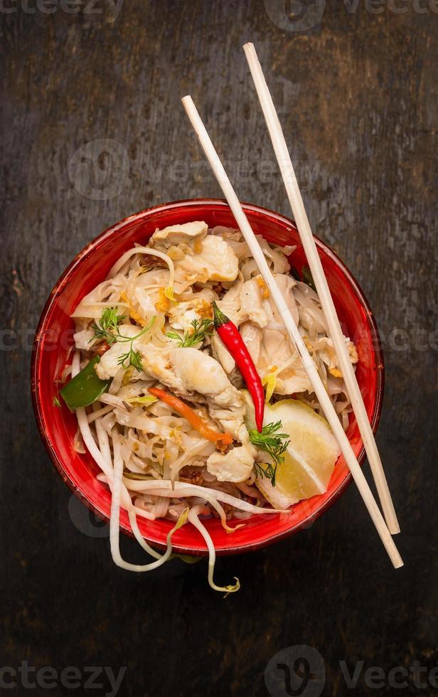 tagliatelle asiatiche con bacchette, pollo e germogli su fondo di legno foto