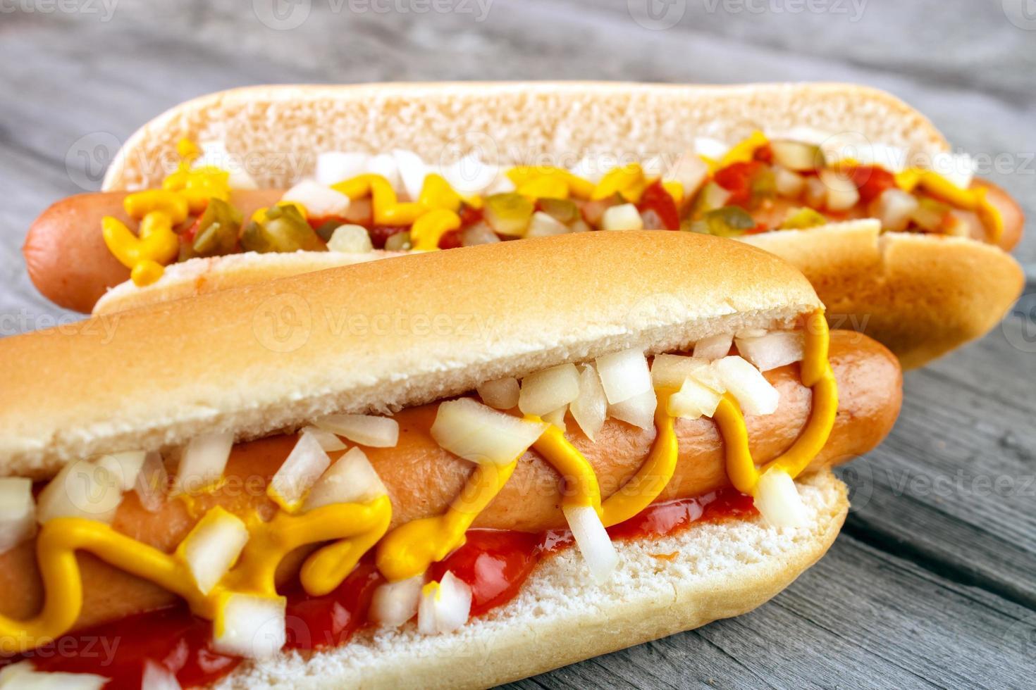 un primo piano di due hot dog con ketchup foto