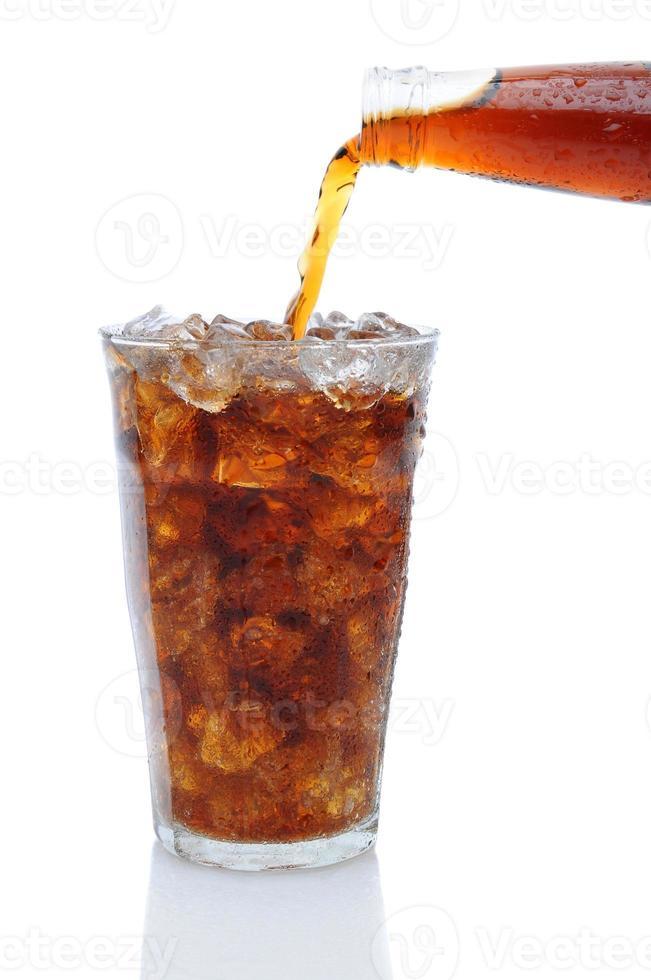 cola che versa dalla bottiglia in un bicchiere di ghiaccio foto