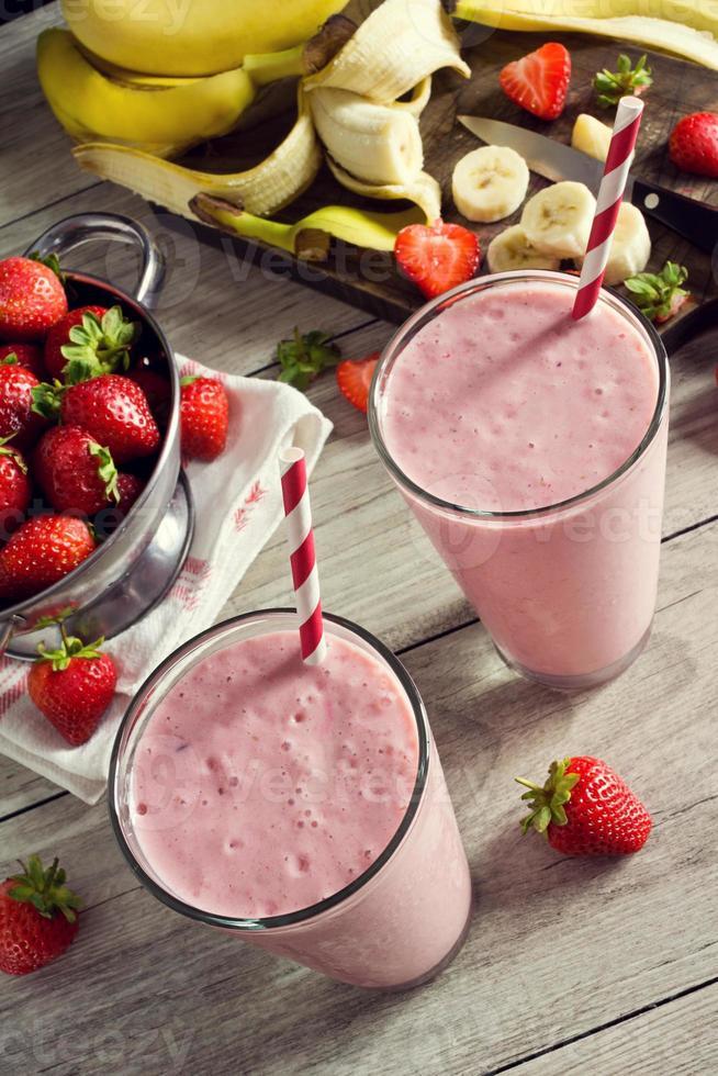 due frullati di yogurt alla banana e fragola in bicchieri con ingredienti foto