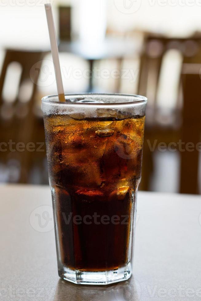 bicchiere di cola con ghiaccio su un tavolo foto